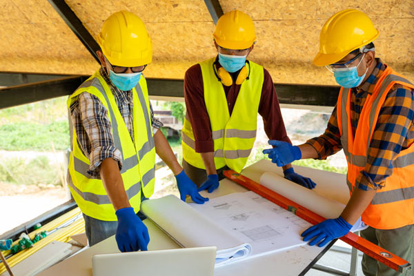 Construction workers on the job of a site protected by wellness covid-19 checks