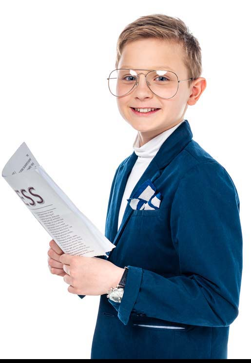 Image of pre-teen boy holding the business news and wearing a suit. He has light hair and glasses.