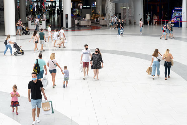 Image of shoppers in an indoor mall. They are social distancing and went through a Wellness Check Services safety scan.