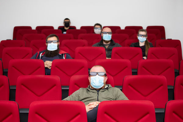 Image of people social distancing at a movie theatre after getting a wellness check for covid