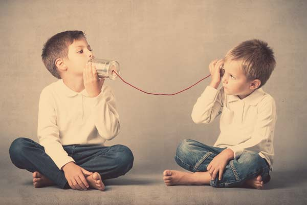 Two boys playing telephone with cans and string