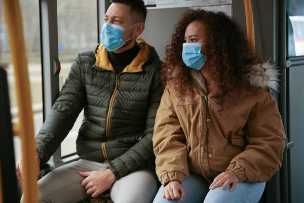 Image of couple sitting on a bus wearing surgical masks